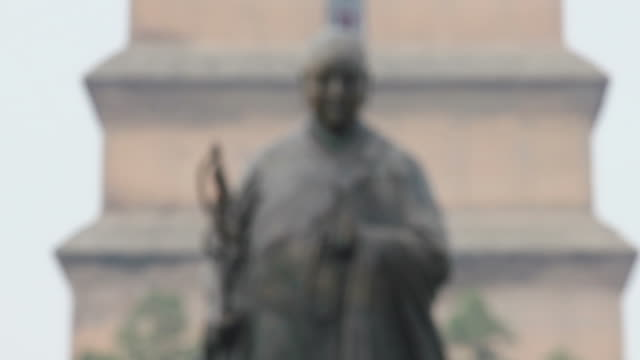 ls r/f statue of master xuan zang and  big wild goose pagoda/xian,shaanxi,china - intoning bildbanksvideor och videomaterial från bakom kulisserna
