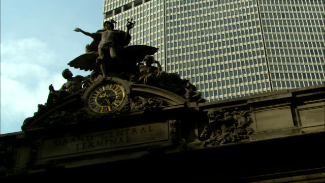 a statue of minerva, mercury, and hercules stands atop the grand central terminal in new york city. - minerva 個影片檔及 b 捲影像