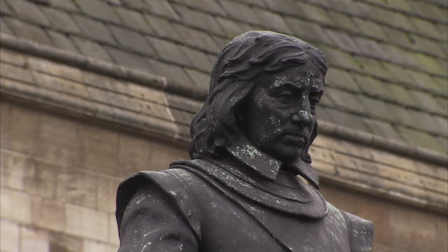 a statue of oliver cromwell stands before the houses of parliament in london england. available in hd. - britisches parlament stock-videos und b-roll-filmmaterial