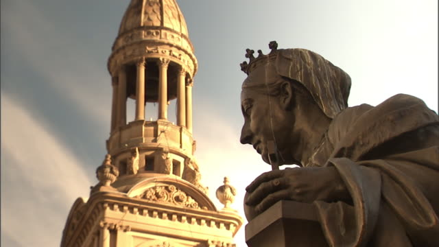 A statue of Queen Victoria accents a street below the Sydney Town Hall clock tower in Australia.
