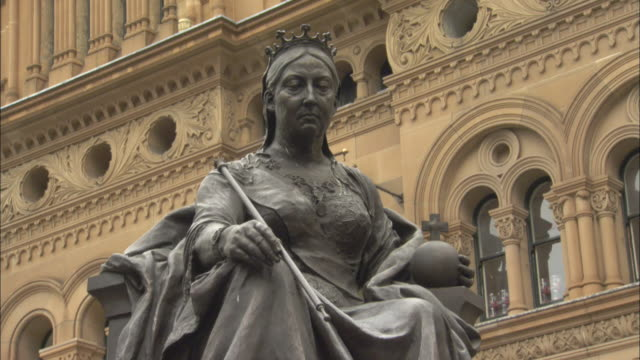 a statue of queen victoria stands in front of the queen victoria building, sydney, australia. - beauty queen stock videos and b-roll footage
