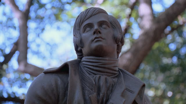 a statue of robert burns rises into the trees along central park's literary walk in new york city. - robert burns poet stock videos & royalty-free footage