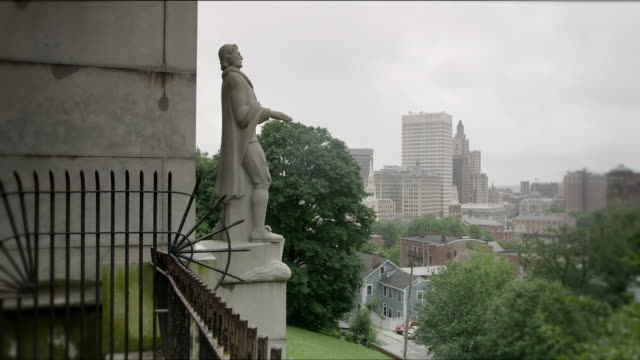 statue of roger williams, founder of rhode island, at prospect terrace park in providence. wide shot from the side of statue with the providence city skyline in distance. camera pans left to right. - male likeness stock videos & royalty-free footage
