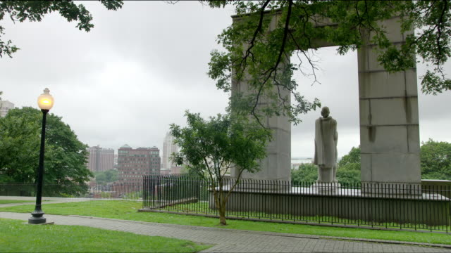 Statue of Roger Williams, founder of Rhode Island, at Prospect Terrace Park in Providence. Wide shot from behind as camera pans from left to right.
