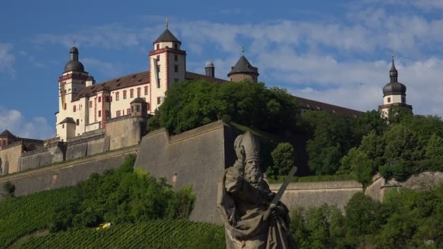 vídeos de stock, filmes e b-roll de statue of saint kilian on the old bridge across river main with marienberg fortress, wuerzburg, lower franconia, bavaria, germany - plano americano