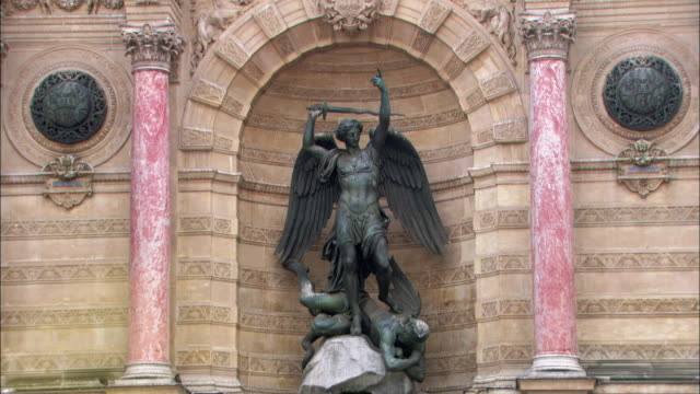 a statue of saint michael stands before a fountain in paris. - statue stock videos & royalty-free footage