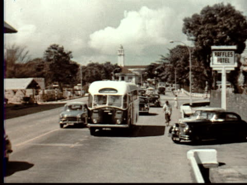 1957 montage statue of stamford raffles, founder of singapore, overlooks bridge + city street w/ traffic + bus stop. malayan airways bus turns into driveway of raffles hotel / singapore / audio - male likeness stock videos & royalty-free footage