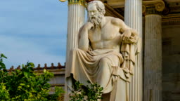 Statue of the Greek philosopher Socrates on a marble chair, background of columns and sky.
