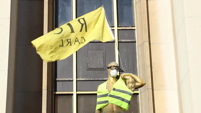 statue of the trocadero esplanade with a yellow vest and a yellow flag ric - yellow stock videos & royalty-free footage