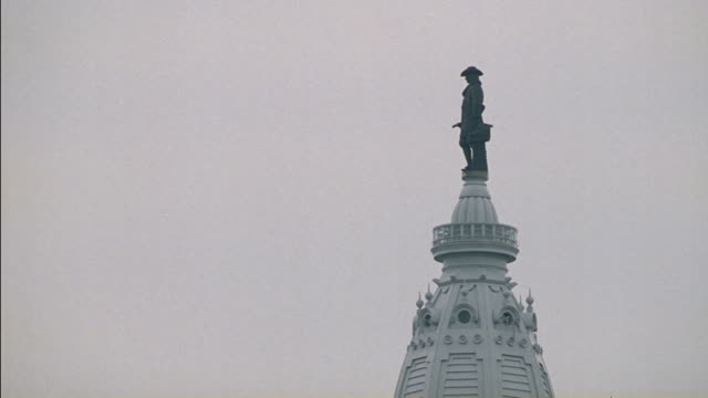 a statue of william penn sits on top of the philadelphia city hall. - william penn stock videos & royalty-free footage