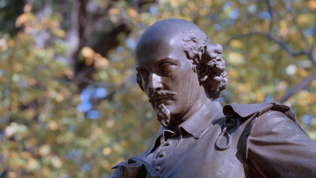 a statue of william shakespeare rises into the trees along central park's literary walk in new york city. - poetry stock videos & royalty-free footage