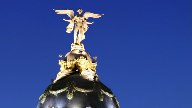 statue of winged goddess victoria lit up atop dome of edificio metropolis at night / zoom out to view of building and time lapse traffic passing on gran via and calle de alcala / madrid, spain - 女神点の映像素材/bロール