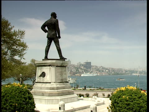 Statue on a plinth of Mustafa Kemel Ataturk staring out to sea town and harbour in background boats pass by Istanbul