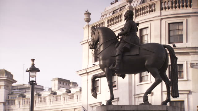 a statue outside trafalgar square depicts charles i on a horse that has one leg upraised. - freizeitreiten stock-videos und b-roll-filmmaterial