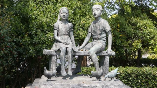 vidéos et rushes de statue showing two kids in nagasaki peace park in japan - arme de destruction massive