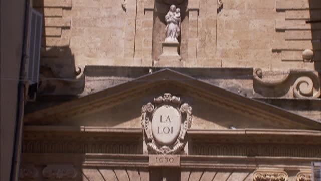 A statue stands in an alcove below a clock tower.