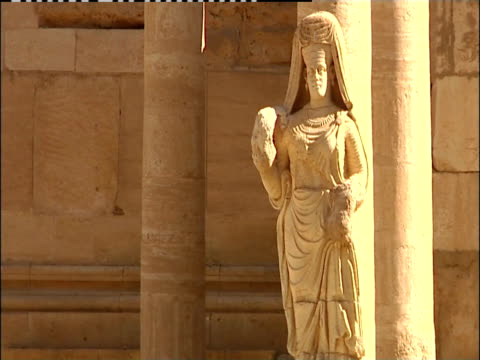 a statue stands near pillars at the great temple in hatra, iraq. - column stock videos & royalty-free footage
