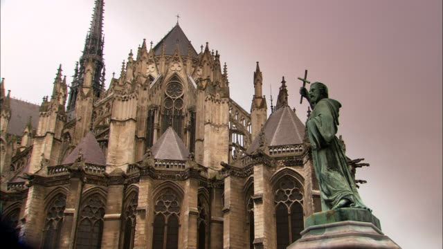 a statue stands outside amiens cathedral. - cattolicesimo video stock e b–roll