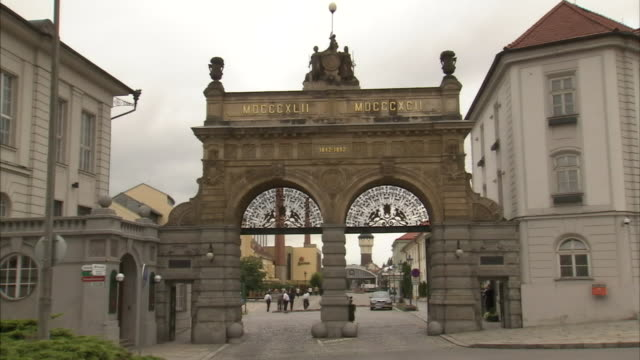 a statue tops a double archway in front of the pilsner urquell brewery. - pilsner stock videos & royalty-free footage