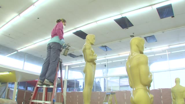 Statues being painted for the Academy Of Motion Picture Arts And Sciences' Oscar Statue Paint Day at the Academy Of Motion Picture Arts And Sciences'...