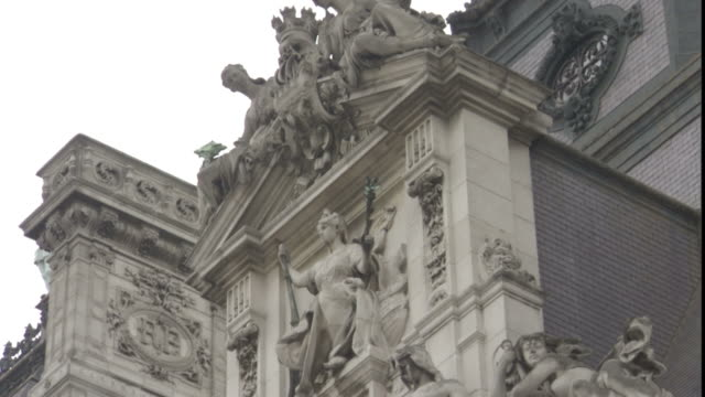 statues decorate the uppermost pediments and towers of the hotel de ville in paris. - hotel de ville paris stock videos & royalty-free footage