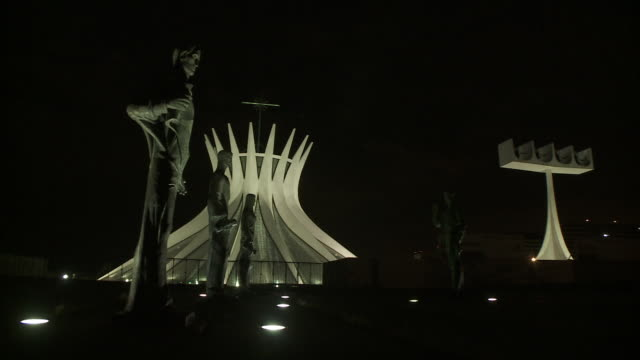 statues line a walkway to the brasilia cathedral at night. - brasilia stock videos and b-roll footage