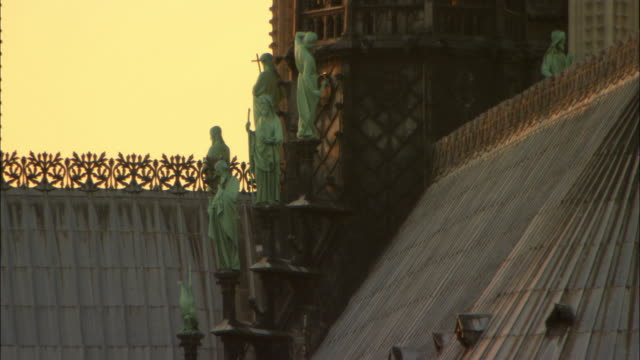 cu statues of saints on rooftop of notre dame cathedral / paris, france - notre dame de paris stock videos and b-roll footage