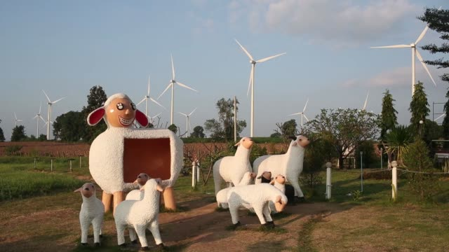 Statues of sheep stand in front of wind turbines outside the Subplu wind farm operated by Gunkul Engineering Pcl in Huay Bong Thailand on Thursday...
