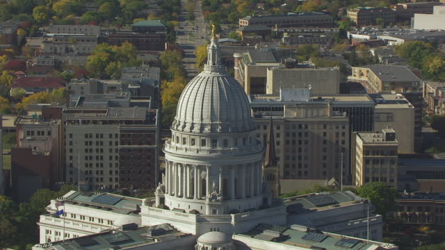 WS ZO AERIAL POV Statues on Wisconsin state capital building with cityscape / Madison, Wisconsin, United States