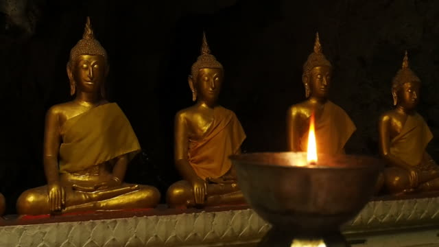 Statuette of Buddha and a burning candle