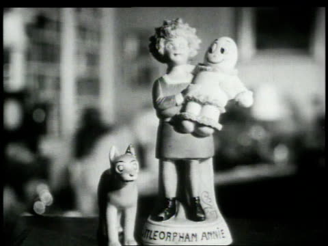 stockvideo's en b-roll-footage met statuettes of little orphan annie and sandy / harold gray working in office - cartoonist