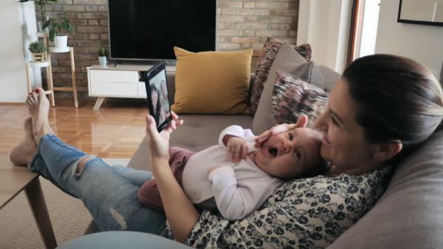 zu hause bleiben und leben retten - frau im gespräch mit familie über videoanruf auf dem handy - single mother stock-videos und b-roll-filmmaterial