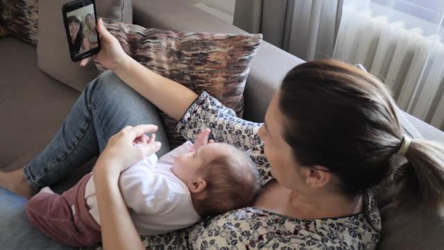 zu hause bleiben und leben retten - frau im gespräch mit verwandten über videoanruf auf dem handy - single mother stock-videos und b-roll-filmmaterial