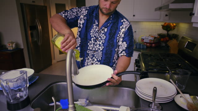 stay at home dad cleans the dishes; a saucepan. med, jib. - abwaschen stock-videos und b-roll-filmmaterial