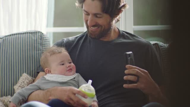 stay at home dad holding baby video chats with smartphone on living room sofa. - handheld stock videos & royalty-free footage