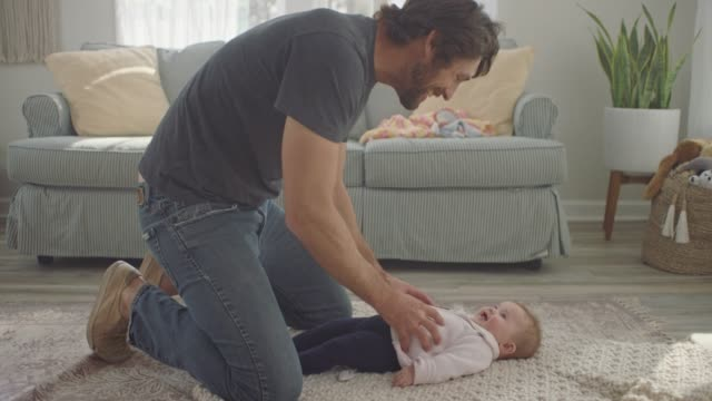slo mo. stay at home dad plays games to make infant daughter laugh as she looks up at him and smiles on living room floor. - tickling stock videos & royalty-free footage