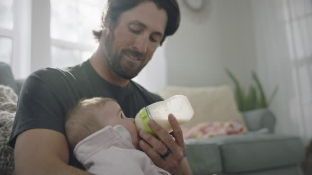 stockvideo's en b-roll-footage met a stay at home dad smiles as he feeds his baby milk from a bottle. - zuigfles