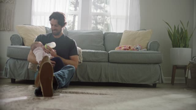 a stay at home dad smiles as he feeds his infant daughter milk from a baby bottle in family living room. - milk bottle stock videos & royalty-free footage