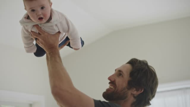 a stay at home dad smiles as he swings and flies infant daughter around sunny living room. - wohnraum stock-videos und b-roll-filmmaterial