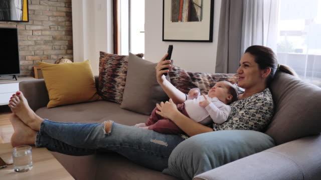bleiben sie zu hause wegen coronavirus - frau im gespräch mit familie über videoanruf auf dem handy - single mother stock-videos und b-roll-filmmaterial