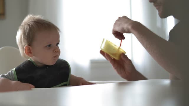 stay at home father feeding his baby son - responsibility stock videos & royalty-free footage
