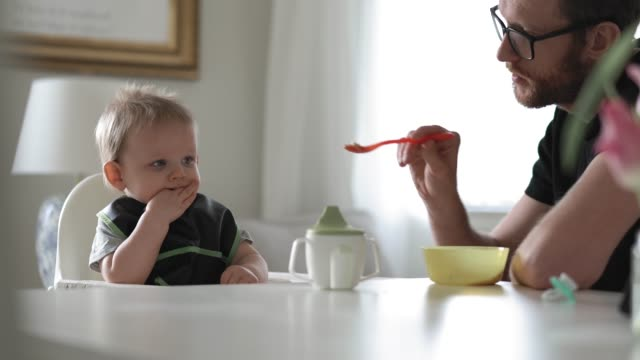 stay at home father feeding his baby son - feeding stock videos & royalty-free footage