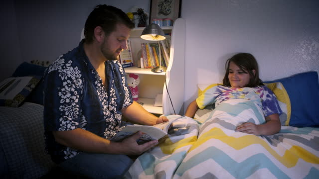 Stay at home father reads to his 10 year old daughter at bedtime - smiling and laughing