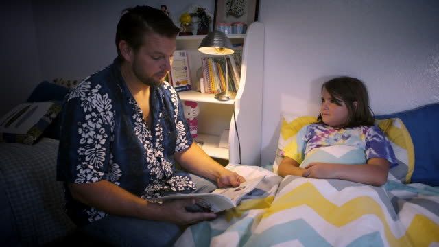 Stay at home father reads to his 10 year old daughter at bedtime - sleepy
