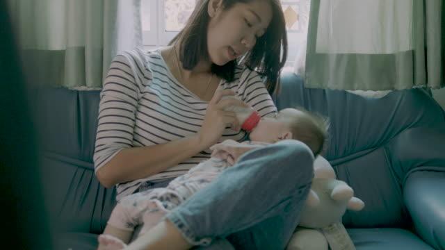 vidéos et rushes de un séjour à la maison maman sourit comme elle nourrit son lait de bébé à partir d'une bouteille. - tenir