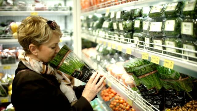 vidéos et rushes de rester à la maison mère achetant des légumes dans le supermarché - 50 54 ans
