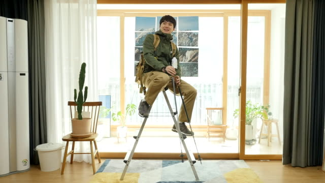 stay at home - young man climbing ladder and feeling like hiking at home - imagination stock videos & royalty-free footage