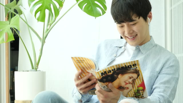 stay at home - young man enjoying his 'hocance' vacation while reading a magazine - 雑誌点の映像素材/bロール