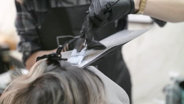 vídeos de stock, filmes e b-roll de fique linda e se ame. mude seu visual. mulher sênior ativa em uma boutique de cabelo. close-up do cabeleireiro aplicando corante de cabelo no cabelo castanho. - brown hair