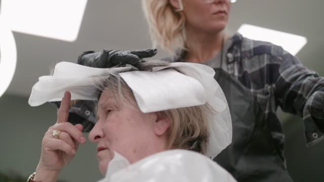 vídeos de stock, filmes e b-roll de fique linda e se ame. mude seu visual. mulher sênior ativa em uma boutique de cabelo. close-up do cabeleireiro aplicando corante de cabelo no cabelo castanho. visão de ângulo baixo - brown hair